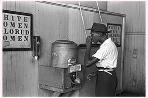 Pictured: An African American man drinks from a water cooler in 1939. Photo by Russell Lee, United States Library of Congress.